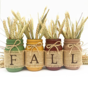 Four mason jars in green, oker, brown and taupe with the letters fall on burlap
