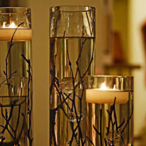 Tall glasses with twigs and floating candles