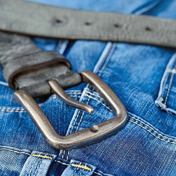 Close up of a dark grey belt on jeans