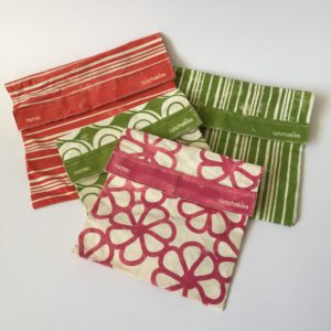 Four Lunchskins: two in green stripes, one in red stripes and one in fuchsia flower pattern