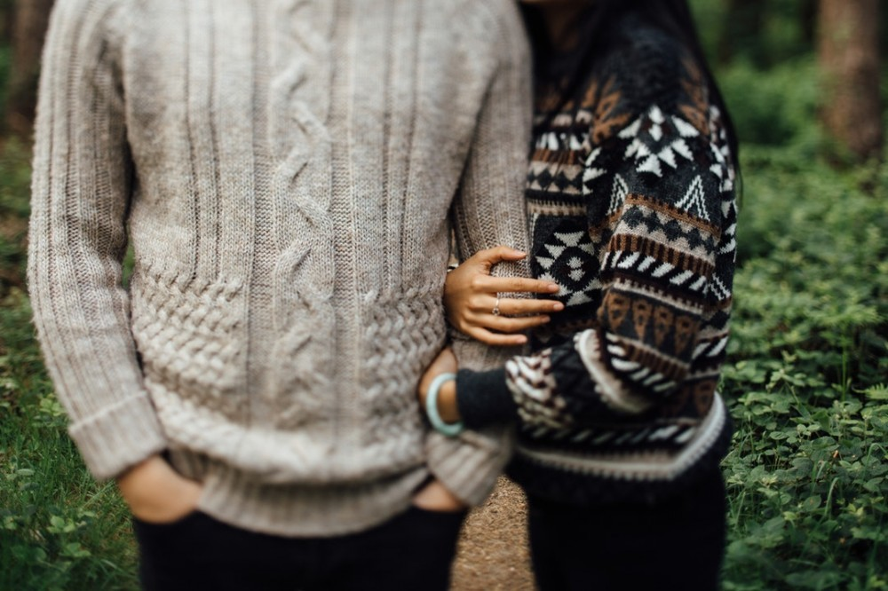 Couple arm in arm wearing warm sweaters