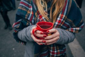Woman holding red cup of coffee