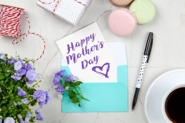 Turquoise envelop with card reading Happy Mother's Day in purple letters