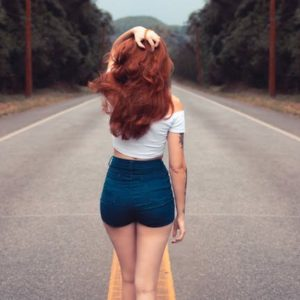 Woman with long red hair wearing blue shorts walking in the middle of the road
