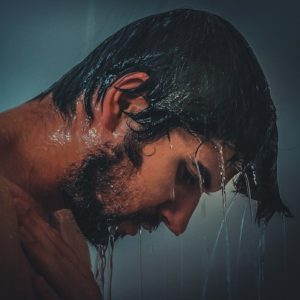 Man with black hair in shower