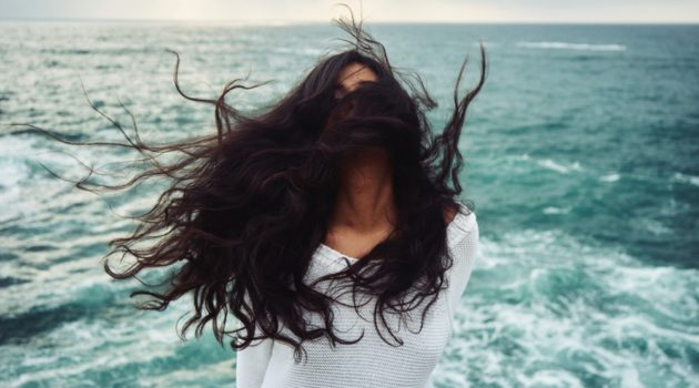 Woman with long black hair waving in the wind by the ocean side