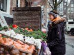 Woman in wintercoat looking at vegetable stall