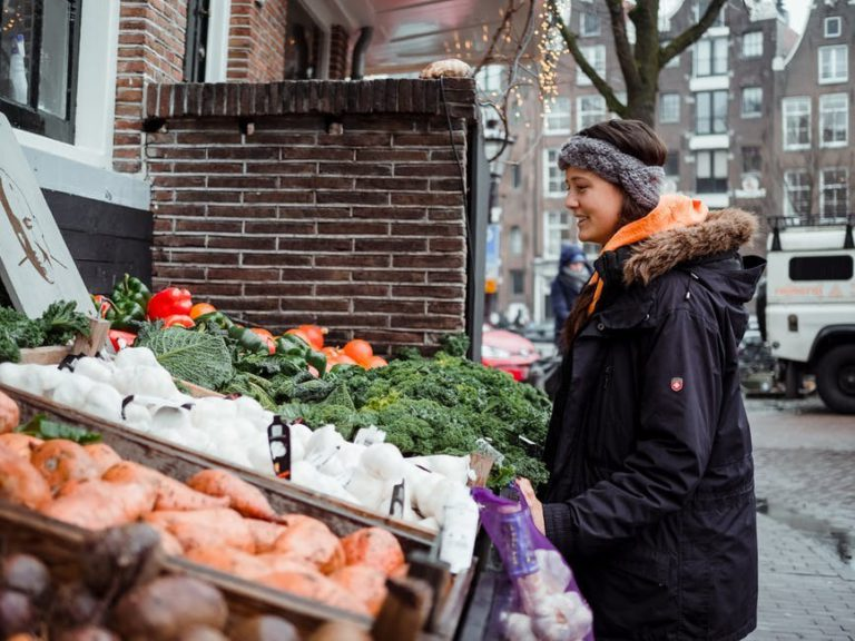 Woman in wintercoat looking at vegetable stall