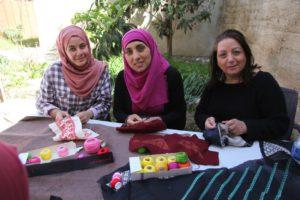 Palistinian women entrepreneurs embroiding fabric for Darzah