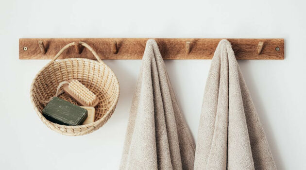 Two beige towels and a natural basket hanging on a wooden coat rack