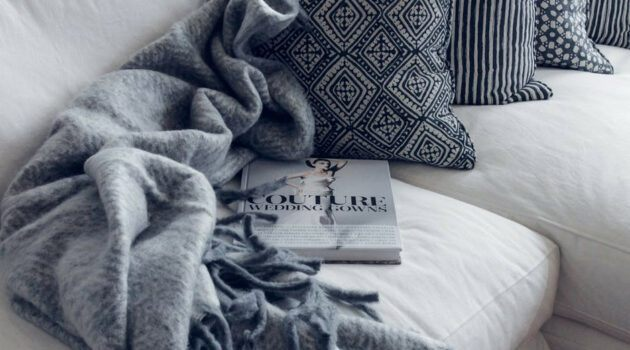 Grey blanket, blue throw pillow and book on an off white couch