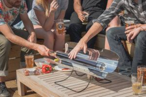 Group of people around the GoSun Sport solar oven while one man touches the tube to show it doesn't get hot