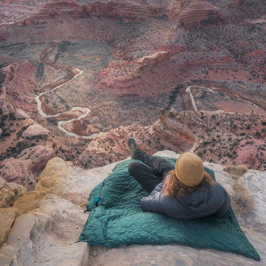Woman laying on Kachula blanket on mountain rock overlooking the valley