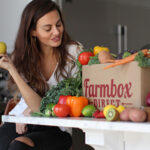 Woman sitting at kitchen bar looking at a big cardboard box from Farmbox Direct filled with fresh vegetables and fruits