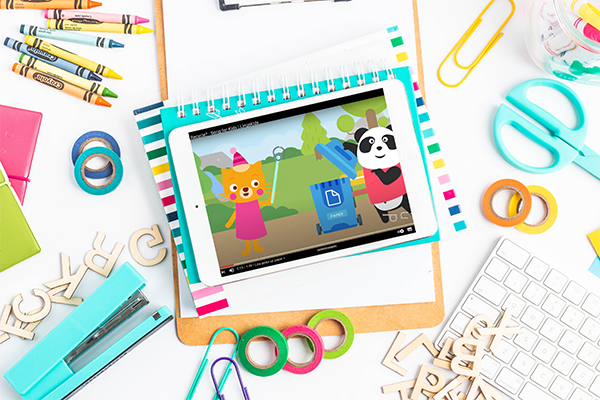 Desk filled with bright colored art supplies and a tablet showing a song about recycling