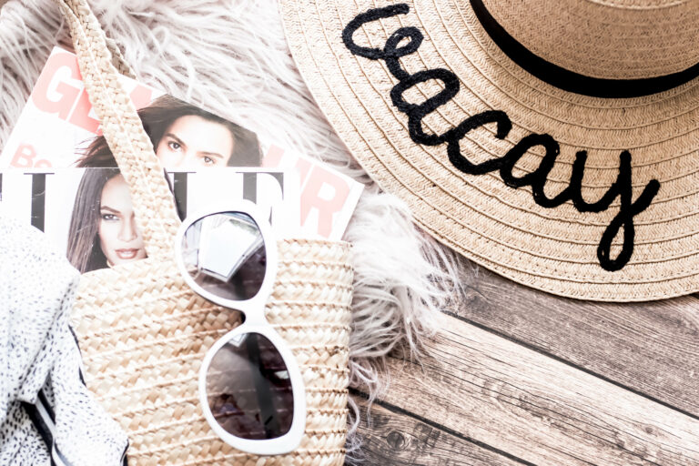 Beach bag with magazines sticking out with a pair of sunglasses on top and next to it a sunhat with Vacay embroided on the wide brim