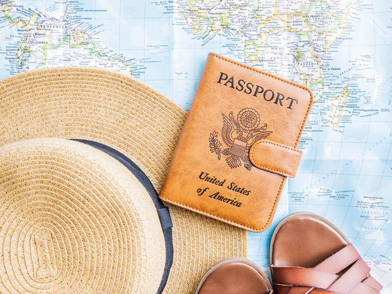 A sun hat, brown sandals, and a brown leather passport holder placed on a world map
