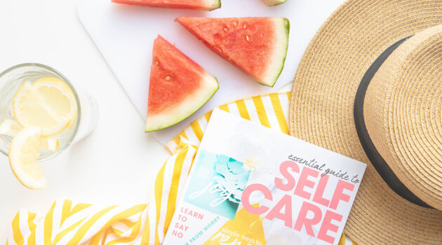 Magazine featuring a selfcare story laying on a table next to a straw hat, slices of water melon and a glass of water with lemon slices